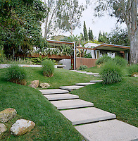In the lush gardens shallow concrete steps wind through lawns and shrubs