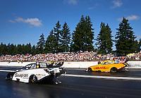 Aug. 4, 2013; Kent, WA, USA: NHRA funny car driver Cruz Pedregon (left) races alongside Del Worsham during the Northwest Nationals at Pacific Raceways. Mandatory Credit: Mark J. Rebilas-USA TODAY Sports
