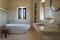 A modern stylish, free-standing 'Egg' bath tub stands in the centre of the tadelakt bathroom. A beaded panel from Mali hangs in one corner.
