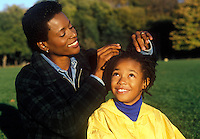 Mother braids her daughters hair.