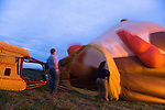 "Hot air balloonists  at the Shenandoah Valley Hot Air Balloon Festival at Historic Long Branch in Millwood, Virginia blow air into the balloon ""envelope.""  After filling the balloon with air, they will fire a propane burner to heat the air.  Since hot air rises, this will eventually cause the balloon to stand up, then fly up."