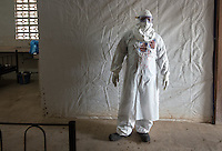 Health care worker Ben Smith, hygienist supervisor, stands in the ETU at ELWA II in Monrovia, Liberia on Monday, March 9, 2015. He is wearing a portrait of himself on his PPE.<br /> Occidental College professor Mary Beth Heffernan's PPE Portrait Project involves creating wearable portraits of the health care workers who must wear PPE (personal protective equipment) when working with patients.<br /> (Photo by Marc Campos, Occidental College Photographer) Mary Beth Heffernan, professor of art and art history at Occidental College, works in Monrovia the capital of Liberia, Africa in 2015. Professor Heffernan was there to work on her PPE (personal protective equipment) Portrait Project, which helps health care workers and patients fighting the Ebola virus disease in West Africa.<br />