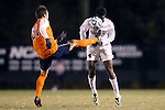 12 November 2013: Virginia's Ryan Zinkhan (21) challenges Wake Forest's Tolani Ibikunle (right) for the ball. The Wake Forest University Demon Deacons hosted the University of Virginia Cavaliers at Spry Stadium in Winston-Salem, North Carolina in a 2013 NCAA Division I Men's Soccer match and the quarterfinals of the Atlantic Coast Conference tournament. Virginia won the game 1-0 in overtime.