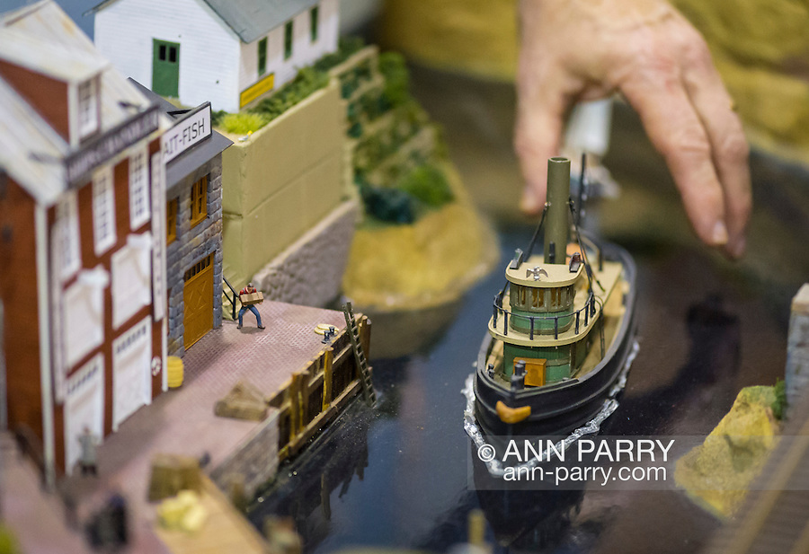 Hicksville, New York, USA. February 22, 2015. Deus ex machina. A model train club member reaches his hand down to position a model boat in an old fashioned dock scene with marine buildings displayed at the Model Train Exhibit hosted by Trainville Hobby Depot at the Broadway Mall, including an N Scale layout, the Long Island HOTrack train club HO scale model train portable modular layout, and others. The person positioning the ship is the club member who built the scene. Donations were accepted at exhibit to support the Nassau County Empire State Games for the Physically Challenged.