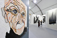 HONG KONG - MARCH 13:  Visitors chat while painting 'Albert Einstein' by Lee Waisler is seen on the left  in art fair Art Central on its preview day on March 13, 2015 in Hong Kong, Hong Kong.  (Photo by Lucas Schifres/Getty Images)