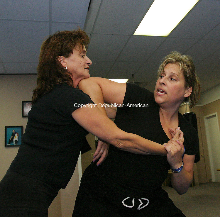 WATERBURY, CT 8/21/07- 082107BZ11- Instructor Tina Perrone, right, demonstrates an elbow stirke to the head of student Janice Pelletier, of Prospect, during a women's self defense class at Blue Line Martial Arts School in Waterbury Tuesday. <br /> Jamison C. Bazinet Republican-American