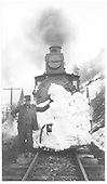 RGS engine with front covered in snow.  Engineer or workman standing to left side.<br /> RGS