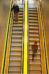 Two individuals ride the yellow escalator at the Seattle Public Library.