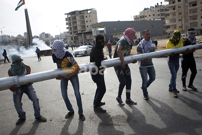 Palestinian protesters set barricades during clashes with Israeli security forces near the Jewish settlement of Bet El, near the West Bank city of Ramallah, on October 13, 2015. A wave of stabbings that hit Israel, Jerusalem and the West Bank this month along with violent protests in annexed east Jerusalem and the occupied West Bank, has led to warnings that a full-scale Palestinian uprising, or third intifada, could erupt. The unrest has also spread to the Gaza Strip, with clashes along the border in recent days leaving nine Palestinians dead from Israeli fire. Photo by Shadi Hatem