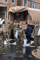 """Army National Guard soldiers (181st Engineer) hand out food and care packages to residents of Chelsea, Massachusetts, at the intersection of Congress Avenue and Hawthorne Street in Chelsea, Massachusetts, on Mon., April 27, 2020. The operation is part of daily pop-up food distribution in the city as part of relief efforts during the ongoing Coronavirus (COVID-19) global pandemic. Chelsea, Mass., is one of the hardest hit communities in Massachusetts with high infection and death rates. As much as 80% of the population works in so-called """"essential jobs,"""" meaning that they continue to work during shelter-in-place orders."""