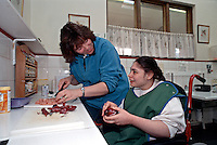 A young lady with learning disabilities being helped by her care assistant in the kitchen. She is being taught how to cook, worktops, sink and cooker have been adjusted to enable her to access them and work unaided as much as possible. This image may only be used to portray the subject in a positive manner..©shoutpictures.com..john@shoutpictures.com