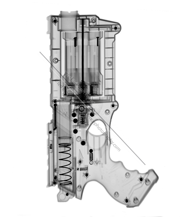 An X-ray of a toy gun. This gun shoots sponge darts out the front when the trigger is pulled.
