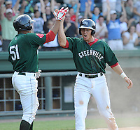 Shortstop Nick Natoli (23) of the Greenville Drive, right, high-fives Henry Ramos after scoring the winning run on a ninth inning walk-off single by Boss Moanaroa that defeated the Asheville Tourists, 5-4, in a game on Sunday, August 26, 2012, at Fluor Field at the West End in Greenville, South Carolina. (Tom Priddy/Four Seam Images)
