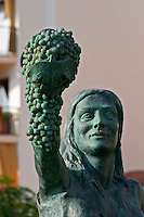 Statue of a girl holding a bunch of grapes and a basket by R Cuello. Detail. Sitges, Catalonia, Spain