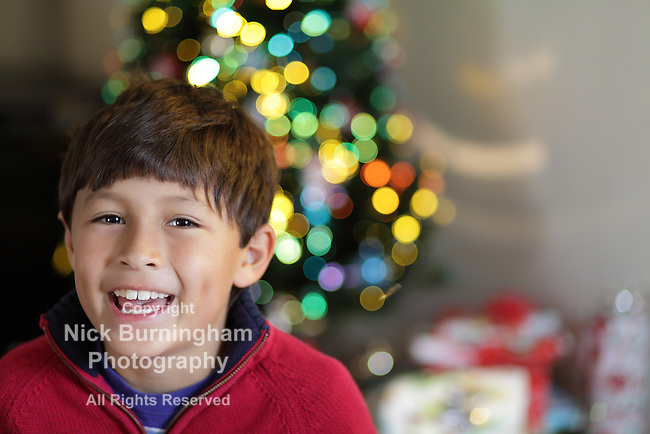 Smiling boy sitting in front of Christmas tree with lights - shallow focus with copy space to right