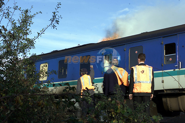 Fire engulfs the roof of the train as members of the Drogheda and Co Louth Fire service fight it..Pic Fran Caffrey Newsfile.©Newsfile Ltd..Copy Elain Keogh