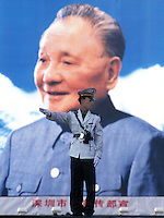 A traffic cop stands in front of a Deng Xiaoping billboard in Shenzhen, China.