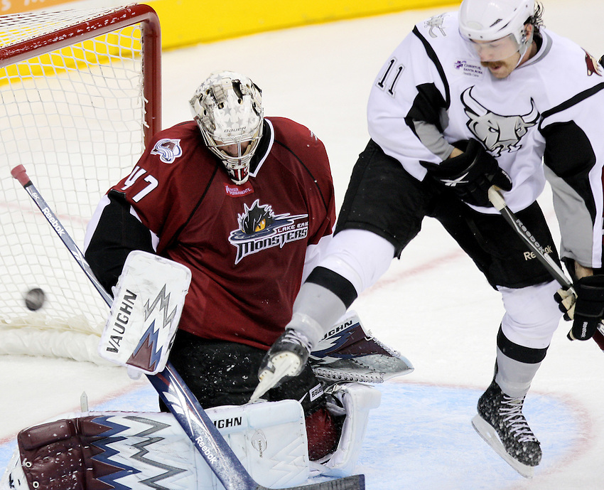 Lake Erie Monsters goaltender John Grahame, left, makes a save as San Antonio Rampage's Ryan Hollweg jumps to allow the puck through during an AHL hockey game, Wednesday, Oct. 20, 2010, at the AT&T Center in San Antonio. (Darren Abate/pressphotointl.com)
