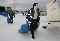 Saturday, Feb. 18, 2006  Anchorage, Alaska. Volunteers bring straw to air force pilot  Cessna planes headed out to checkpoints along the trail.  Each musher is given one bale of straw at a checkpoint to bed their dogs down.