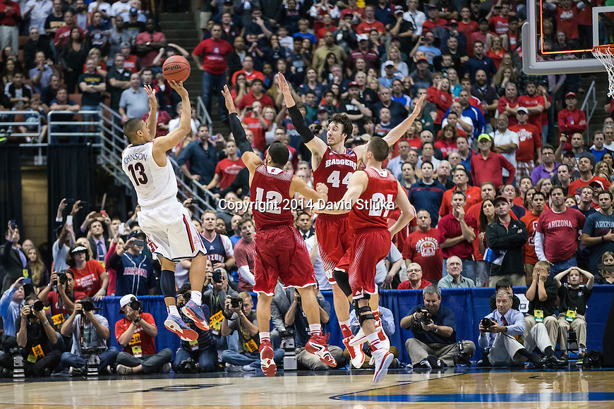 Wisconsin Badgers Traevon Jackson (12), Frank Kaminsky (44) and Josh Gasser (21) defend the last shot of the game from Arizona Wildcats guard Nick Johnson (13) during the Western Regional Final NCAA college basketball tournament game Saturday, March 29, 2014 in Anaheim, California. The Badgers won 64-63 (OT). (Photo by David Stluka)