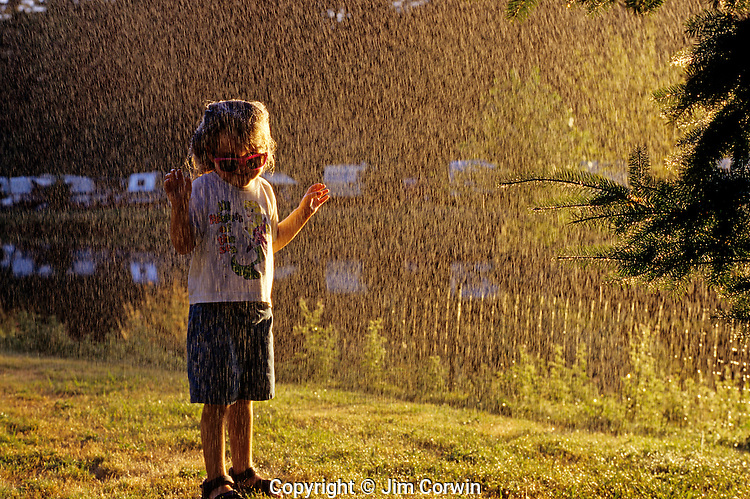 Sunset with girl playing in yard during a summer shower.