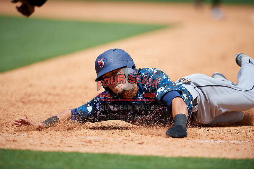 Jacksonville Jumbo Shrimp center fielder Yefri Perez (12) dives back to first base during a game against the Birmingham Barons on April 24, 2017 at Regions Field in Birmingham, Alabama.  Jacksonville defeated Birmingham 4-1.  (Mike Janes/Four Seam Images)