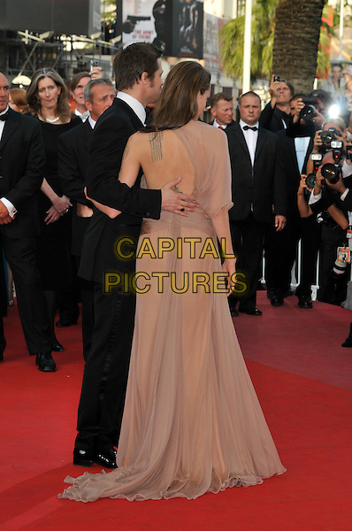 "BRAD PITT & ANGELINA JOLIE.The ""Inglourious Basterds"" Premiere at the Grand Theatre Lumiere during the 62nd Annual Cannes Film Festival, Cannes, France..May 20th, 2009.full length black tuxedo suit cream beige brown pink dress sheer long one shoulder tattoos arm around waist couple back behind rear .CAP/PL.©Phil Loftus/Capital Pictures."