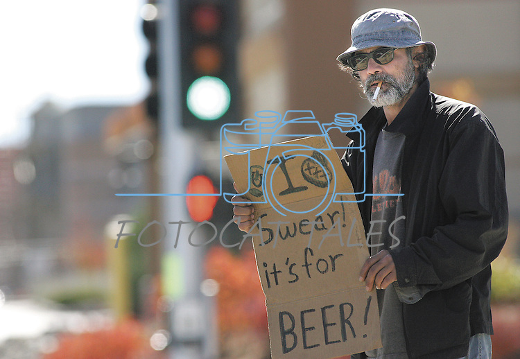 "Jeff Husla panhandles in Carson City, Nev., on Oct. 19, 2007. The other side of Husla's sign says, ""Taking over planet - need funds."" Passing through the area, he says, ""the money's nice, but I like seeing them (drivers) smile."" .Photo by Cathleen Allison/Copyright Nevada Appeal"