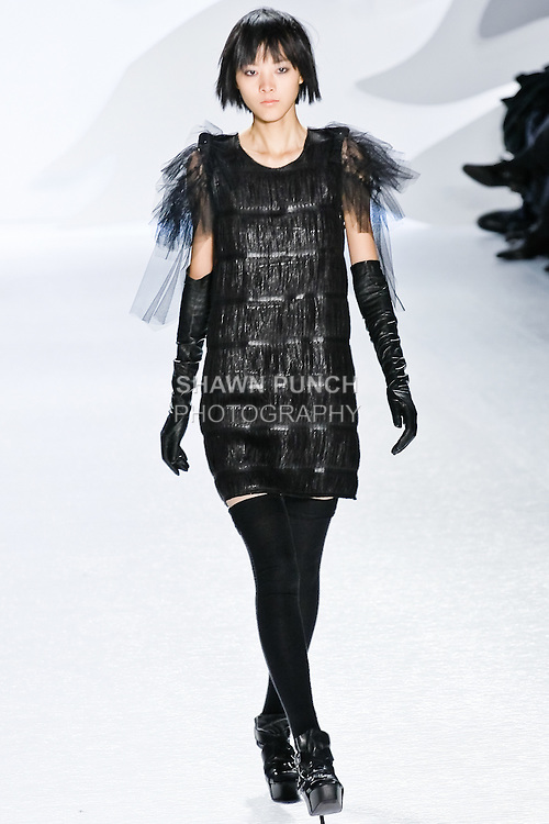 Emma Pei walks runway in a black coated fringe dress with tulle rosette sleeves and charcoal felt epaulettes at  the Vera Wang Fall 2010 fashion show during Mercedes-Benz Fashion Week.