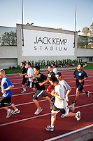 Runners run by the new sign for Jack Kemp Stadium, April 26, 2011. (Photo by Marc Campos, Occidental College Photographer)