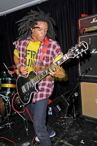 Dee Radke of Radkey <br /> performing in concert, The Blackeart, Camden, London, England. <br /> 17th October 2013<br /> on stage in concert live gig performance performing music half length red check shirt yellow top guitar 3/4 jeans denim <br /> CAP/MAR<br /> &copy; Martin Harris/Capital Pictures
