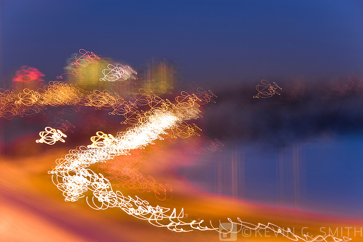 Abstract of the Anchorage skyline at twilight with the lights from rush hour traffic on Minesota blvd. in the foreground, winter, Southcentral Alaska, USA.