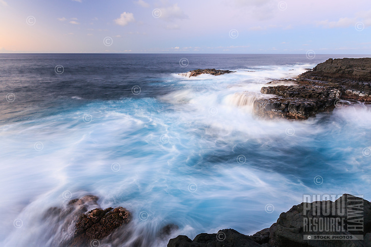 At sunset, the ocean overflows in a rush of waves and tiny waterfalls at Queen's Bath in Princeville, Kaua'i.