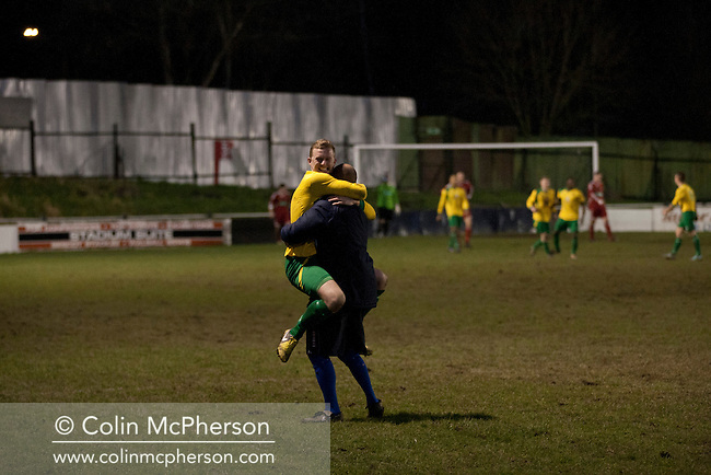 Home manager Ian Rowe and defender Pete Wood celebrating the club's decisive fourth goal at Garden Walk Stadium, during the FA Vase 4th round tie between Gornal Athletic (in yellow) from Dudley in the West Midlands and visitors Wisbech Town. Gornal, from the Midland Alliance and appearing for the first time at this stage of the tournament, defeated Wisbech, who play in the Eastern Counties League, by 4-2 after extra-time, after the visitors had lead two-nil after 10 minutes. The FA Vase was a nationwide, non-League English football tournament for semi-professional clubs and the winner of this tie played away at Bodmin Town in the next round.