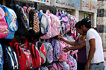 Palestinians walk past school bags as vendors display them in the preparation of new school year in a market in the West Bank city of Nablus on Sept. 03, 2011. The Palestinian students in the West Bank and Gaza Strip will start their studing on 03 September 2011. Photo by Wagdi Eshtayah