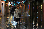 A tourist walk with boots on flooded streets during an acqua alta (high-water). The Acqua Alta, a convergence of high tides and a strong sirocco, reached 125 centimetres in Venice, on November 20, 2013.  <br /> <br /> &copy; Pierre Teyssot