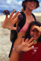 Mother and daughter with sea urchin shells on their fingers playing on beach