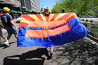 "Phoenix, Arizona (March 29, 2014) - A woman demonstrator marches as she holds an Arizona flag with the ""Equality"" symbol. Photo by Eduardo Barraza © 2014"