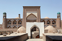 General view of the Qutlugh Murad Inaq Madrasah, 1804-12, Khiva, Uzbekistan, pictured on July 7, 2010, in the morning. The Qutlugh Murad Inaq Madrasah is the first completely two-storey masrasah in Khiva comprising 81 hujras. The building is composed along the longitudinal axis with a four-ayvan yard and connected with residential hudjras for students and teachers. Qutlugh Murad Inaq madrasah is the only monument in Khiva where non-glazed relief-stamped terracotta was used. Corner guldasta of the main facade are decorated with terracotta tiles with non-recurring pattern. Khiva, ancient and remote, is the most intact Silk Road city. Ichan Kala, its old town, was the first site in Uzbekistan to become a World Heritage Site(1991). Picture by Manuel Cohen.