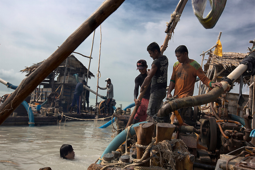 Indonesia - Bangka Island - Rebo - Miners sucking the tin out of the seabed with bamboo sticks a few hundred meters off the coast. The diver comes in and out of the water in order to help placing the bamboo stick at the right place before starting to suck the tin. Around 50 miners work feverishingly on these pontoons from 8am until 5 pm, each one of them earn around 15US$ per day, a much more profitable activity than fishing. Risks of land sliding are extremely high, every year around 60 workers die covered with sand. The turquoise waters have turned brown and muddy and a cloud of black smoke surrounds the pontoons due to the pollution caused by the mining.