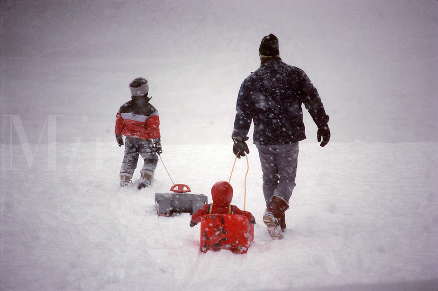 Father and children with sledding.