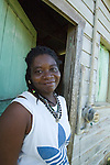 Garifuna craftswoman wearing handmade jewlrey outside her hut in Barranco village, southern Belize