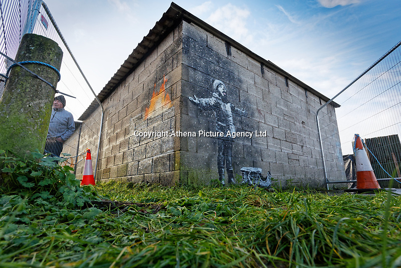 "Pictured: The Banksy graffiti on a garage in Port Talbot, Wales, UK. Thursday 20 December 2018<br /> Re: The artist Banksy has confirmed that a new graffiti piece that has appeared in Port Talbot, south Wales is his.<br /> He announced on Instagram: ""Season's greetings"" - with a video of the artwork in the Taibach area of Port Talbot.<br /> The image appears on two sides of a garage in a lane near Caradog Street, depicting a child enjoying snow falling - the other side reveals it is a fire emitting ash.<br /> The owner of the garage said he had not slept over fears it might be vandalised."
