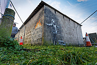 Pictured: The Banksy graffiti on a garage in Port Talbot, Wales, UK. Thursday 20 December 2018<br /> Re: The artist Banksy has confirmed that a new graffiti piece that has appeared in Port Talbot, south Wales is his.<br /> He announced on Instagram: &quot;Season's greetings&quot; - with a video of the artwork in the Taibach area of Port Talbot.<br /> The image appears on two sides of a garage in a lane near Caradog Street, depicting a child enjoying snow falling - the other side reveals it is a fire emitting ash.<br /> The owner of the garage said he had not slept over fears it might be vandalised.