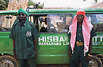 Hispah Sharia Police, a volunteer religious militia force, enforcing Sharia law. The bearded police volunteer is knicknamed Osama Bin Africa..The implementation of Islamic Sharia Law across the twelve northern states of Nigeria, centres upon Kano, the largest Muslim Husa city, under the feudal, political and economic rule of the Emir of Kano. Islamic Sharia Law is enforced by official state apparatus including military and police, Islamic schools and education, plus various volunteer Militia groups supported financially and politically by the Emir and other business and political bodies. Fanatical Islamic Sharia religious traditions  are enforced by the Hispah Sharia police. Deliquancy is controlled by the Vigilantes volunteer Militia. Activities such as Animist Pagan Voodoo ceremonies, playing music, drinking and gambling, normally outlawed under Sharia law exist as many parts of the rural and urban areas are controlled by local Mafia, ghetto gangs and rural hunters. The fight for control is never ending between the Emir, government forces, the Mafia and independent militias and gangs. This is fueled by rising petrol costs, and that 70% of the population live below the poverty line. Kano, Kano State, Northern Nigeria, Africa