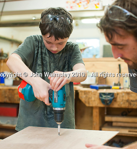 One of the kids with Will Redhead, woodwork teacher, using a powerdrill to put in a screw, Summerhill School, Leiston, Suffolk. The school was founded by A.S.Neill in 1921 and is run on democratic lines with each person, adult or child, having an equal say.  You don't have to go to lessons if you don't want to but could play all day.  It gets above average GCSE exam results.
