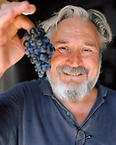 CROATIA, Hvar, portrait of vintner Andro Tomic holding grape and smiling in his winery on Hvar Island.