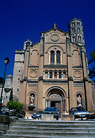 The facade of a church with a tower in the background. France.