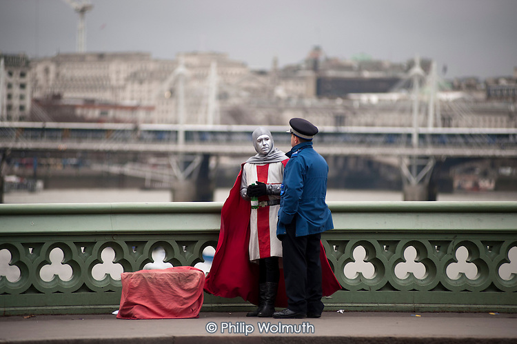 A mime artist dressed as a crusader and a Police community Support Officer on Westminster Bridge, London.