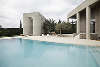 View over the swimming pool to the monumental concrete pool house situated at a short distance from the house